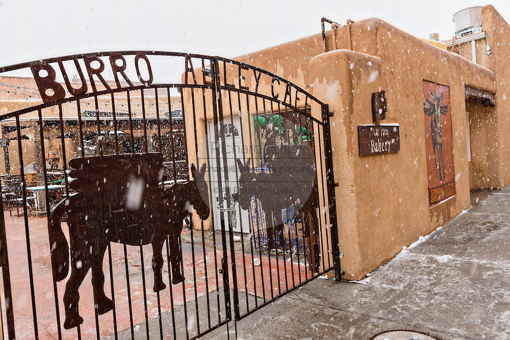 Burro Alley once known for brothels and saloons in the old west during a winter snow in Santa Fe, New Mexico. Before automobiles almost all goods were transported into the mountain town by pack animals.