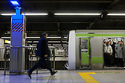 A salaryman or Japanese office worker rushes for a train past blue lights installed at all 29 JR Yamanote Line stations for a cost of 15 million Yen (165,000 USD) in an effort to decrease suicides by people jumping under trains. Over 2,000 people jumped under trains in 2008, accounting for 6% of all suicides in the country. The blue LED lights are meant to calm and soothe potential jumpers, though there is little scientific evidence for this. Japan has one of the highest suicide rates in the world which the recent economic crisis has exacerbated. Shinagawa Station, Tokyo, Japan December 4th 2009