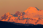 The setting sun reddens the southwestern face of Mount Baker, a 10,781 foot (3,286 meter) volcano located in Whatcom County, Washington state. Mount Baker, which is part of the Cascade Range of mountains, has the second-most thermally active crater in the range, second only to Mount St. Helens. Baker's volcanic cone is relatively young, possibly less than 100,000 years old, even though the area where it sits has been volcanically active for 1.5 million years.
