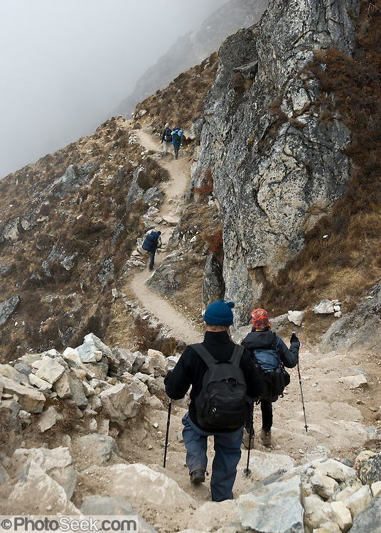 Trekkers walk a trail across a steep hillside between Pangboche and Phortse, in Sagarmatha National Park, Nepal. Sagarmatha National Park was created in 1976 and honored as a UNESCO World Heritage Site in 1979.