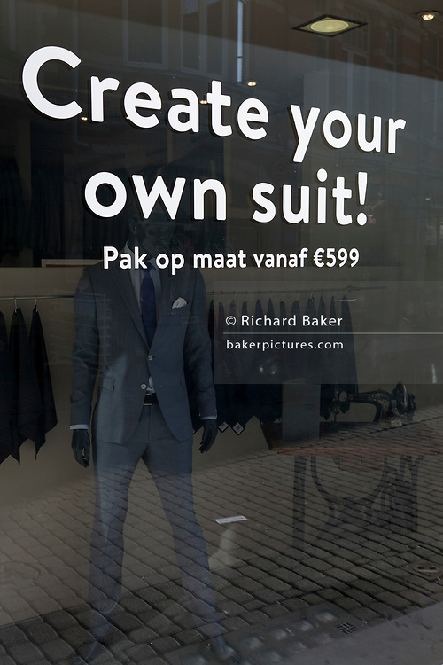 Bi-lingual languages of English and Flemish in a menswear suits shop window, on 24th March 2017, in Leuven, Belgium.