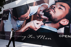 Man walks past shop front poster for barber shop at the Fashion Avenue , housing high-end shops and shopping with luxury brands, in Dubai, United Arab Emirates.