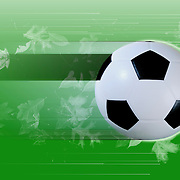Soccer ball on a green background filled with leaves and blur and light streaks to depict balls motion .
