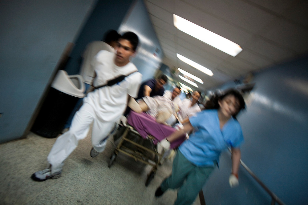 Medicine students and paramedics carry a man  with firearm injuries to the operating room after entering in the emergency of the San Juan de Dios hospital, Guatemala City, Wednesday, May  5, 2010. (AP Photo/Rodrigo Abd)