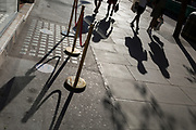 With a further 154 UK covid deaths reported in the last 24hrs, bringing the total to 43,081 victims during the Coronavirus pandemic, more shops are re-opening according to the easing government lockdown restrictions and the shadows of social distancing rope barriers and of shoppers are seen on the pavements of Oxford Street, on 24th June 2020, in London, England.