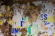 Burned and peeling bus shelter posters in rural village of Neron, Eure-et-Loir, France.