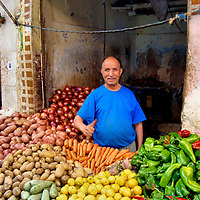 Merchant in Vegetable Stand at Old Medina in Casablanca, Morocco<br /> This shopkeepers&rsquo; vegetable stall looked like a burnt-out bunker. Yet he was extremely proud of his display of potatoes, onions, carrots, bell and chili peppers plus lemons and squash.  It deserved a thumb up.  He is typical of the merchants you will find in the Old Medina: hard working, humble and eager to satisfy every customer.