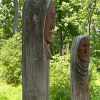 Recreation of a ceremonial circle of wooden poles carved with faces.