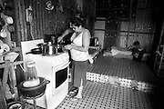 Laura cooks a stew for her family in their new home in the slum. Her youngest son Obed has just returned from school and his on his bed bored with nothing to do but begin homework.