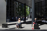 Women sit in a small area of sunlight on Fenchurch Avenue in the City of London - the capital's financial district, on 6th June 2018, in London, England.