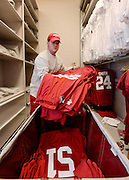 Equipment managers work in the Mal Moore Athletic Facility to get the University of Alabama football team ready for the trip to Baton Rouge to face LSU.  Student equipment manager Thomas Hall packs game jerseys into a container for the trip to LSU.  Normally he would be packing the white jerseys for the road trip but LSU wears white jerseys as their home color.  Photo by Gary Cosby Jr.