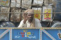 19 OCT 2001, ISLAMABAD/PAKISTAN:<br /> Mann faehrt auf der Ladeflaeche eines LKWs in Begleitung von alten Faessern und Kanistern durch die Strassen von Islamabad<br /> IMAGE: 20011019-02-050