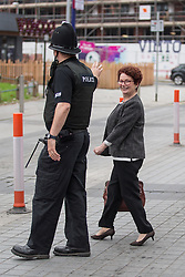 © Licensed to London News Pictures . 20/09/2014 . Manchester , UK . A policeman helps outgoing Salford MP Hazel Blears across the road . Departures at the funeral of Heywood and Middleton MP Jim Dobbin at Salford Cathedral today (Saturday 20th September 2014) . Photo credit : Joel Goodman/LNP