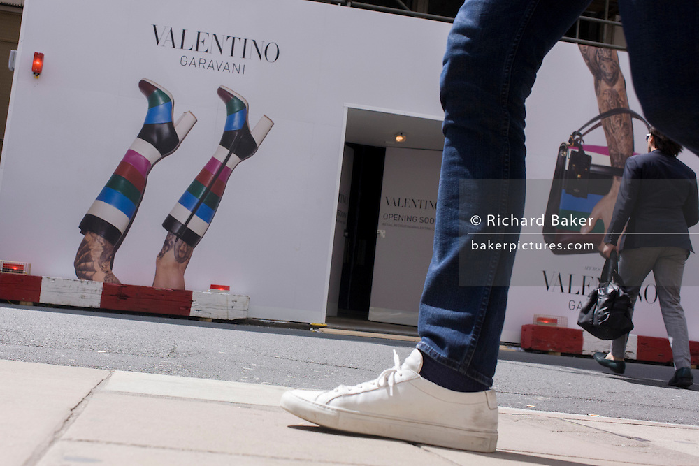 Legs and another person infront of construction hoarding, a part of the forthcoming fashion label, Valentino Garavani's new shop in New Bond Street, central London.