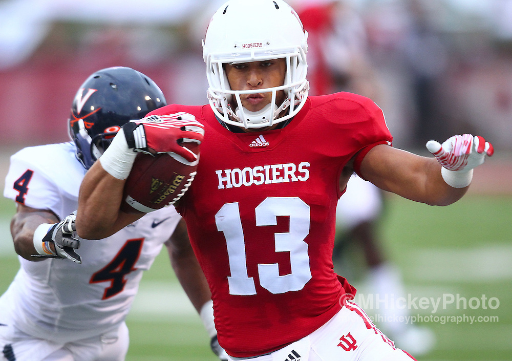 Sept. 10, 2011; Bloomington, IN, USA; Indiana Hoosiers wide receiver Kofi Hughes (13) runs the ball as Virginia Cavaliers safety Rodney McLeod (4) pursues from behind at Memorial Stadium. Mandatory credit: Michael Hickey-US PRESSWIRE