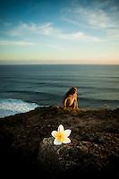 A monkey and a frangipani catch the light of the sun near Uluwatu Temple, Bali, Indonesia.