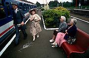 A couple just off the train from Waterloo are en-route to Ascot racecourse on Ladies Day at Royal Ascot racing week. Not looking particularly happy to have arrived, two elderly women look at the clothes worn including the man's top hat and tails. Royal Ascot is held every June and is one of the main dates on the sporting calendar and English social season. Over 300,000 people make the annual visit to Berkshire during Royal Ascot week, making this Europe's best-attended race meeting. There are sixteen group races on offer, with at least one Group One event on each of the five days. The Gold Cup is on Ladies' Day on the Thursday. There is over £3 million of prize money on offer.
