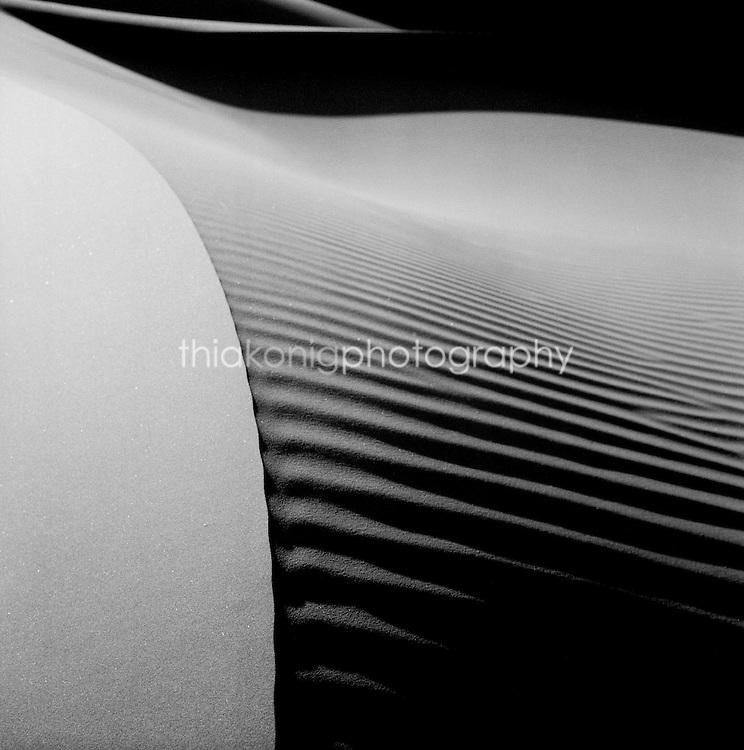 Black and white fine art (medium format film) dramatic light on the sublime curves of the Sossusvlei sand dunes, the Namib desert, Namibia, Africa.