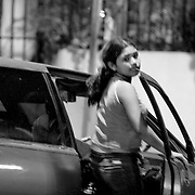 "Rozievel, 15, pregnant, is a child prostitute. She gets into a customers car on a main street in downtown Managua, Nicaragua. ""I do this to help my mother, she is a diabetic. My father left us when I was nine and we have no other alternatives. My mother knows what I do. I used to sell goods at the market but I didn't make enough money. I sold cigarettes and water in bags. I had a friend who also worked in the market and she suggested I come with her.""..""I was raped when I was 13 by two guys. It was seven in the evening and I was on my way home from the market when they raped me. These two men used to live in the neighborhood where we used to live. We had problems with these men. (After the rape) I stayed home for a month without going out. We needed money so we borrowed some but we were in so much debt I decided to go to the streets.""..""Two months after I started working she (mother) asked me how I got money and I told her. My mom is 60 and a diabetic and she can't work. She agreed there was no other alternative. I finished third grade. I dropped out when we didn't' have any money. ..I go out every night and I make 100 -150 Cordoba's/night. ."