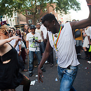 A woman challenges two men to dance to a bongo drum band in Portobello Road. The Notting Hill Carnival has been running since 1966 and is every year attended by up to a million people. The carnival is a mix of amazing dance parades and street parties with a distinct Caribbean feel