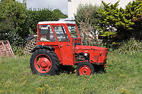 Old red tractor parked in a field on Inis Oirr the Aran Islands in Galway Ireland