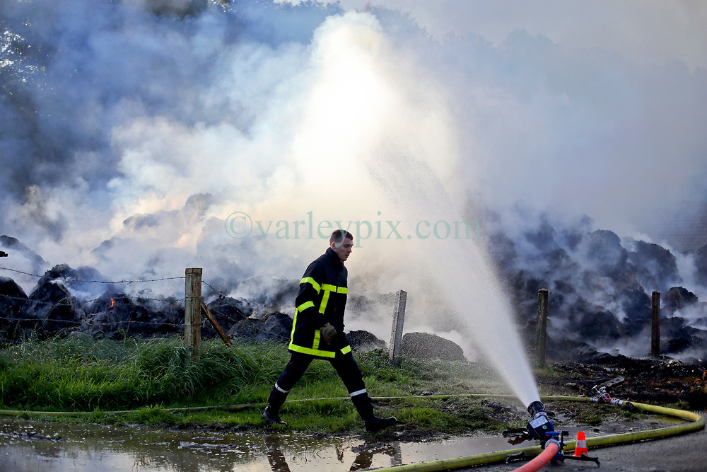 20 Sept 2019. St Denoeux, Pas de Calais, France.<br /> Barn fire. Local fire brigades from Montreuil Sur Mer and Hucqueliers attend a barn fire which destroyed a local farmer's entire winter hay supply for his cattle.<br /> Photo©; Charlie Varley/varleypix.com