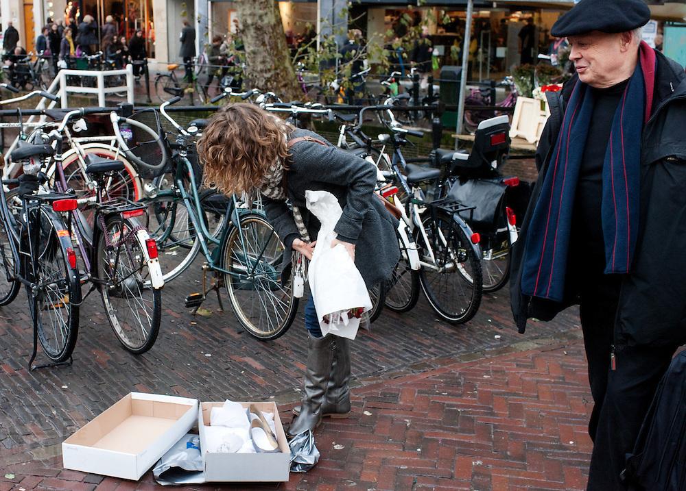 Een meisje trekt midden op straat haar nieuwe schoenen aan.<br /> <br /> A girl is changing shoes in the center of Utrecht