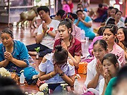 "06 APRIL 2015 - CHIANG MAI, CHIANG MAI, THAILAND:  Family members in the prayer hall at Wat Pa Pao during the ordination of the boys on the last day of the three day long Poi Song Long Festival in Chiang Mai. The Poi Sang Long Festival (also called Poy Sang Long) is an ordination ceremony for Tai (also and commonly called Shan, though they prefer Tai) boys in the Shan State of Myanmar (Burma) and in Shan communities in western Thailand. Most Tai boys go into the monastery as novice monks at some point between the ages of seven and fourteen. This year seven boys were ordained at the Poi Sang Long ceremony at Wat Pa Pao in Chiang Mai. Poy Song Long is Tai (Shan) for ""Festival of the Jewel (or Crystal) Sons.  PHOTO BY JACK KURTZ"