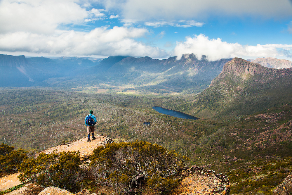 A hiker on the way up Mt Ossa high above Pinestone valley with the Du Cane Range in the background, Cradle Mountain - Lake St Clair National Park.