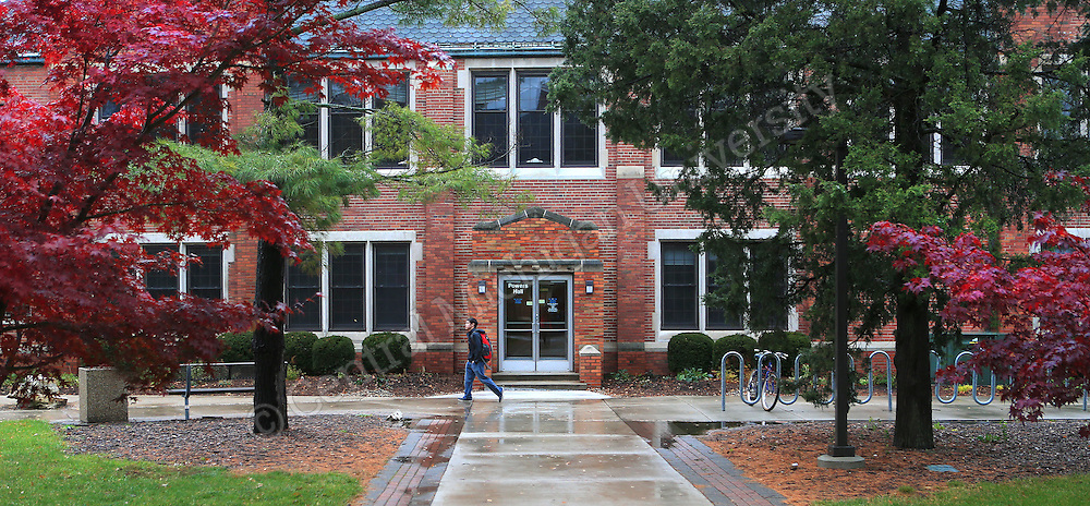 A student  walks between past Powers Hall on a rainy fall day.  scenic. Central Michigan University photo by Steve Jessmore