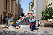 A security guard opens a No Entry barrier for a motor rickshaw to drive out onto the street at TDI Mall, Delhi, India.  (photo by Andrew Aitchison / In pictures via Getty Images)