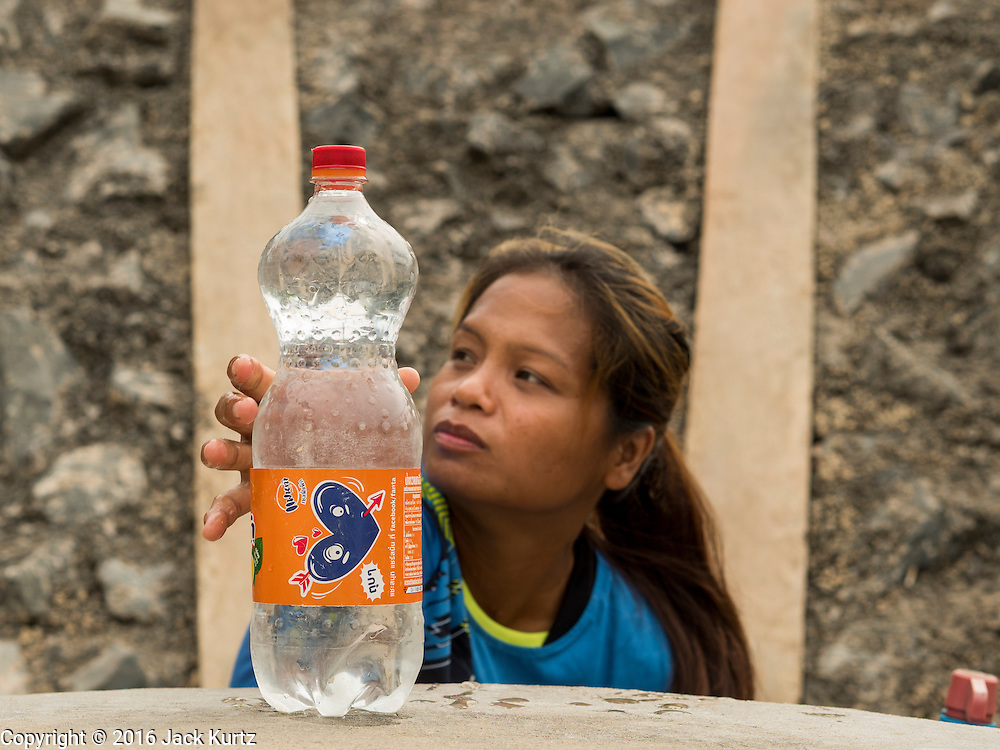 10 MAY 2016 - TA TUM, SURIN, THAILAND:    A woman reaches for a recycled soft drink bottle she filled with water from the artesian well in Ta Tum, Surin, Thailand. The well is the most important source of drinking water for thousands of people in the communities surrounding it.  In the past many of the people had domestic water piped to their homes or from wells in their villages but those water sources have dried up because of the drought in Thailand. Thailand is in the midst of its worst drought in more than 50 years. The government has asked farmers to delay planting their rice until the rains start, which is expected to be in June. The drought is expected to cut Thai rice production and limit exports of Thai rice. The drought, caused by a very strong El Nino weather pattern is cutting production in the world's top three rice exporting countries:  India, Thailand and Vietnam. Rice prices in markets in Thailand and neighboring Cambodia are starting to creep up.    PHOTO BY JACK KURTZ