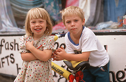 Brother and sister standing together outside shop,