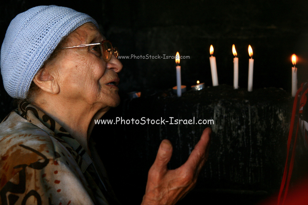 Israel, Upper Galilee, An old lady prays and lights candles, a common ritual at the House of Rabbi David Vemoshe (David Moshe), a jewish pilgrimage site in Zefat (Safed)