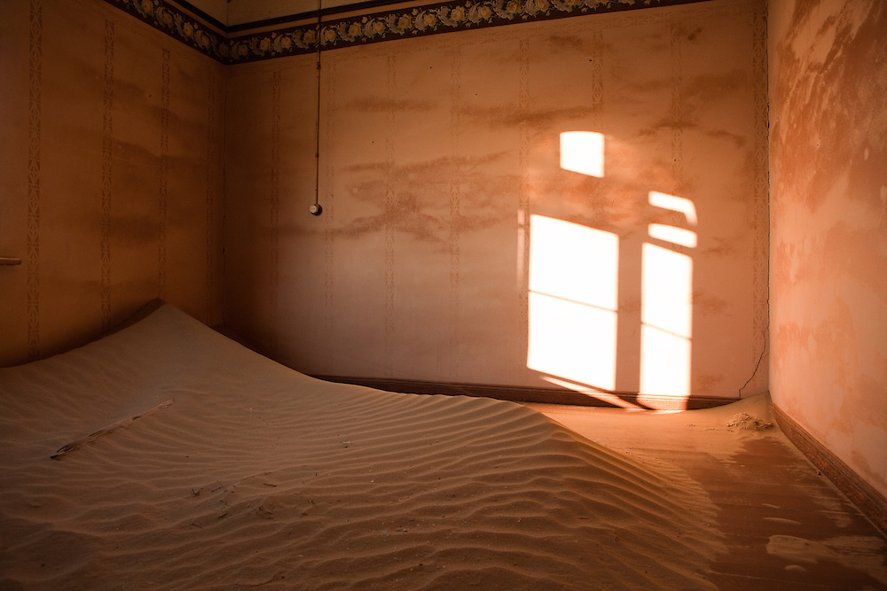 A lone lightswitch, wallpaper and stencilwork contrast with the sand and decay in this abandoned home, in Kolmanskop, Namibia