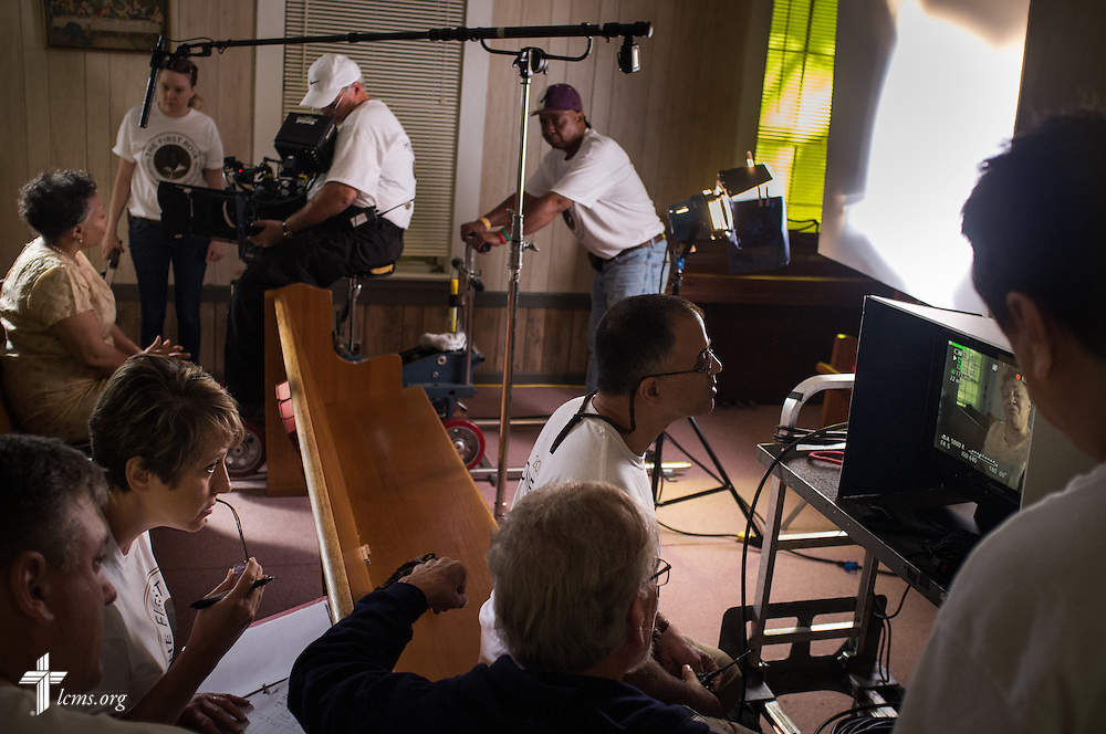 Ben DeSousa, director of photography, intently watches as actress Yvette Jones-Smedley (far left in rear pew), performing the role of Rosa Young, performs during filming of 'The First Rosa' documentary at Hope Lutheran Church on Wednesday, Sept. 24, 2014, near Selma, Ala. DeSousa is joined by (L-R) Kim and the Rev. Dr. Jon Vieker and Dr. Ardon Albrecht, director of the film.  LCMS Communications/Erik M. Lunsford