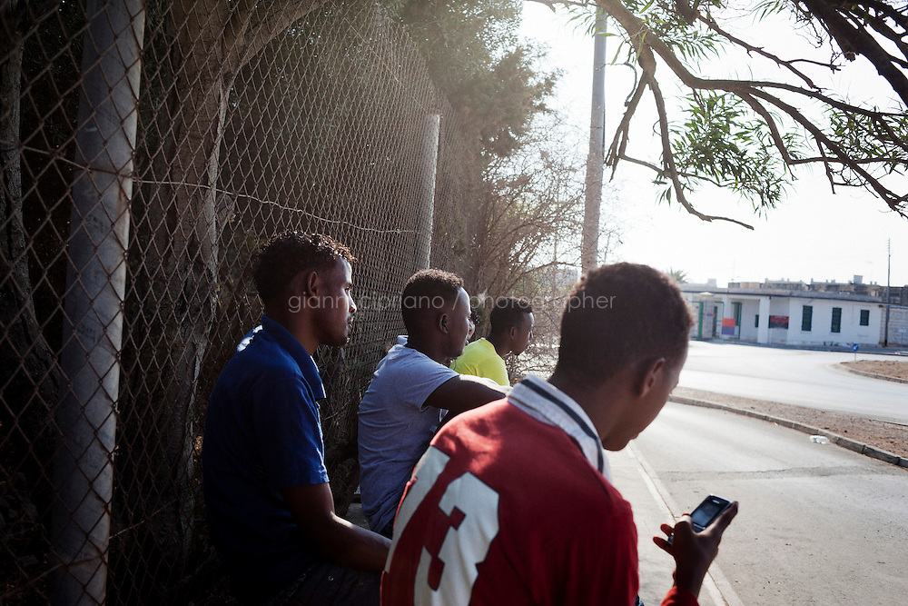 Hal Far, Malta - 21 August, 2012:  Somali migrants wait to be picked up to be hired as day laborers in front of the Hal Far Tent Village open centre, in Hal Far, Malta, on 21 August, 2012.<br /> <br /> The Hal Far Tent Village, initially composed of tents when it first opened, is composed today of 100 containers with no water where the immigrants live for months, and sometimes years. Hal Far (which translates as &quot;Rat's Town&quot;) is an industrial area of Malta which hosts two open centres for immigrants. The open centres in Malta serve as a temporary accomodation facility, but they ended becoming permanent accomodation centres, except for those immigrants who receive subsidiary protection or refugee status and that are sent to countries such as the United States, Germany, Poland, and others. All immigrants who enter in Malta illegally are detained. Upon arrival to Malta, irregular migrants and asylum seekers are sent to one of three dedicated immigration detention facilities. Once apprehended by the authorities, immigrants remain in detention even after they apply for refugee status. detention lasts as long as it takes for asylum claims to be determined. This usually takes months; asylum seekers often wait five to 10 months for their first interview with the Refugee Commissioner. Asylum seekers may be detained for up to 12 months: at this point, if their claim is still pending, they are released and transferred to an Open Center.<br /> <br /> Gianni Cipriano for The New York Times