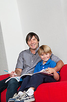 Portrait of father and son doing homework together while sitting on sofa