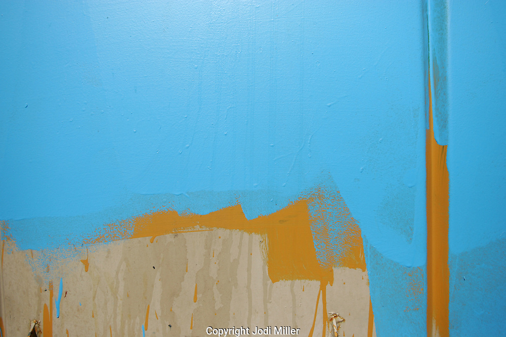 Blue and yellow paint on the side of a wall.
