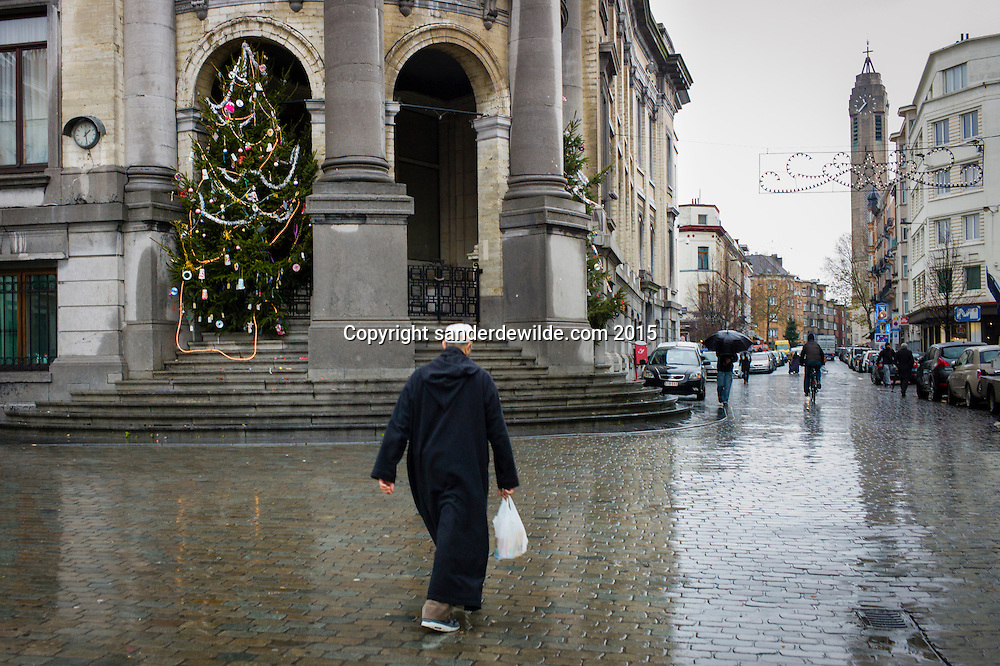 Belgium, Brussels, Sint Jans Molenbeek. 11 December 2015.  Molenbeek, the community of Brussels where terrorists of the Paris attacks lived.A man in religious clothing walks on the main square with the town hall and christmas tree in the background. The John the Baptist church in the far right. (Sander de Wilde for National Post)(For story by Matthew Fischer, foreign correspondent)