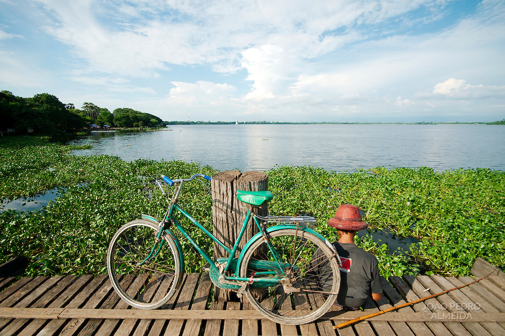 Man fishing at U Bein bridge with his bike parked near him