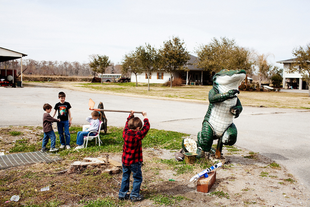 Spencer Bonnecarrere, 6, chops at the dirt in front of the office of Daneco Alligator Farm in Houma, Louisiana on Thursday, February 18, 2010 as his siblings Stephen Paul, 10, Stuart, 5, and cousin Victoria Bourg, 6, play in the background.