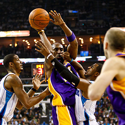 December 29, 2010; New Orleans, LA, USA; Los Angeles Lakers shooting guard Kobe Bryant (24) is defended by New Orleans Hornets point guard Chris Paul (3) and small forward Trevor Ariza (1) as he passes the ball to point guard Steve Blake (5) during the first quarter at the New Orleans Arena.   Mandatory Credit: Derick E. Hingle