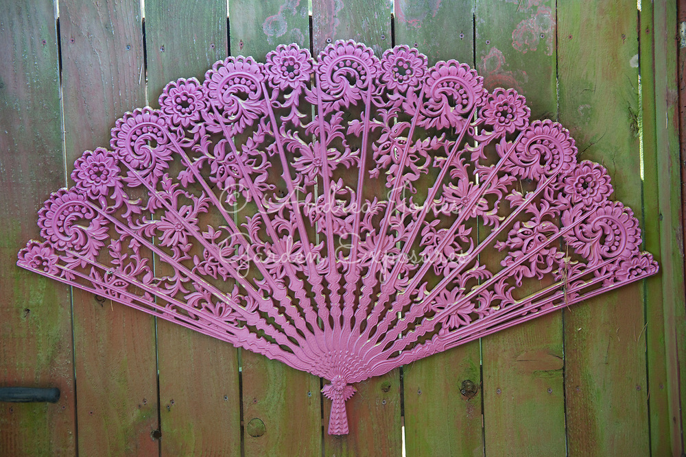 Pink metal fan attached to fence<br /> <br /> <br /> Nancy Goldman's recycled garden (Nancyland), Portland, OR, USA