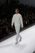 A men's outfit with blue pants and an off-white sweater by Richard Chai at the Spring 2013 Mercedes Benz Fashion Week show in New York.