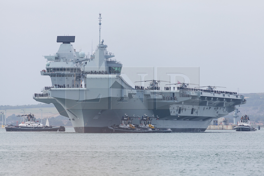 © Licensed to London News Pictures. 18/08/2018. Portsmouth, UK.  The Royal Navy's flagship, HMS Queen Elizabeth, sailing out of Portsmouth Naval Base this evening, 18th August 2018.  The 65,000 tonne aircraft carrier has set sail for an 11-week trip to perform trials with the F-35B aircraft off the coast of the United States.  Photo credit: Rob Arnold/LNP