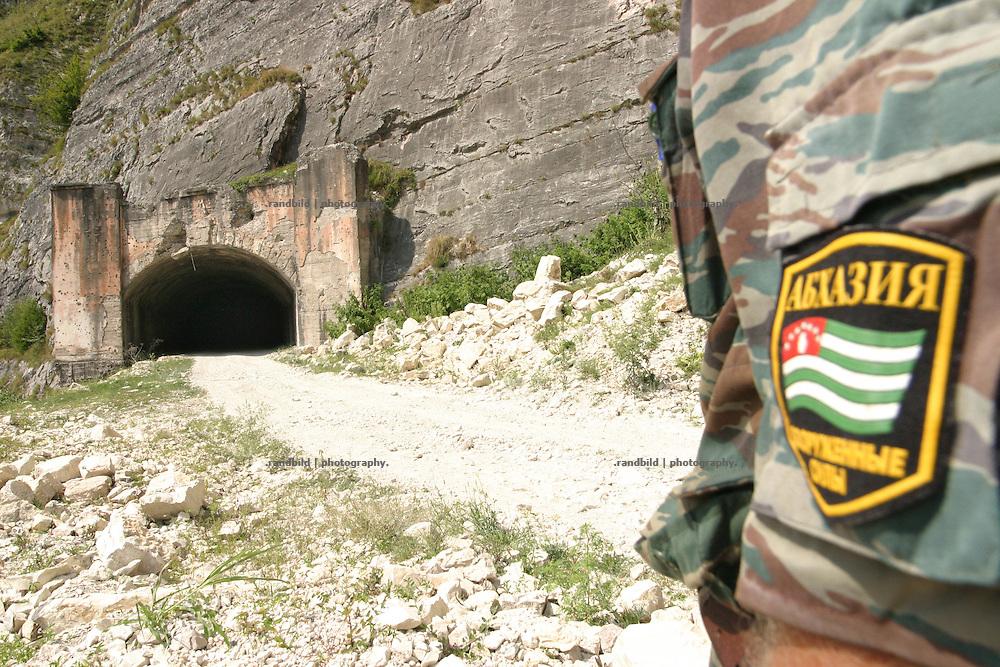 Georgien/Abchasien, Kodori, 2006-08-28, Ein Hauptmann der abchasischen Armee steht vor einem strategisch wichtigen Tunnel im umkämpften abchasischen Kodorital. Abchasien erklärte sich 1992 unabhängig von Georgien. Nach einem einjährigen blutigen Krieg zwischen den Abchasen und Georgiern besteht seit 1994 ein brüchiger Waffenstillstand, der von einer UNO-Beobachtermission unter personeller Beteiligung Deutschlands überwacht wird. Trotzdem gibt es, vor allem im Kodorital immer wieder bewaffnete Auseinandersetzungen zwischen den Armee der Länder sowie irregulären Kämpfern. (A captian of the abkhazian army stands in front of a stategic important tunnel in abkhazian Kodori gorge. Abkhazia declared itself independent from Georgia in 1992. After a bloody civil war a UNO mission observing the ceasefire line between Georgia and Abkhazia since 1994. Nevertheless nearly every day armed incidents take place in the Kodori gorge between the both armys and unregular fighters )