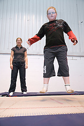 Visually impaired boy with teacher at trampolining youth group event run by NRSB,