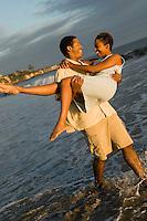 Man carrying woman at ocean
