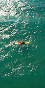 Aerial view of lifeguard paddling on ocean, vertical perspective